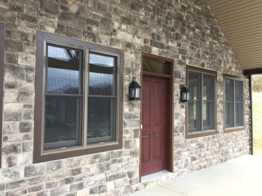 The front porch full stone wall, three windows and burgundy front door.