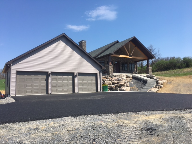The front of the home with a three car garage and a front porch, surrounded by countryside fields and mountains.