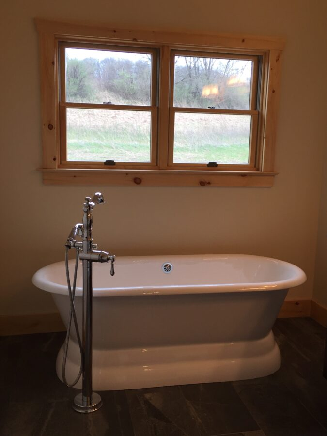 The Master Bathroom's cast Iron, freestanding tub with a Delta, floor-mount tub-filler faucet