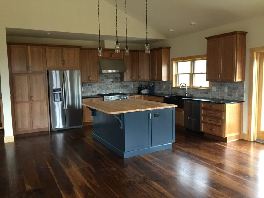 The kitchen with hardwood floors, an island with a butcher-block countertop, stainless steel appliances and wood cabinetry.