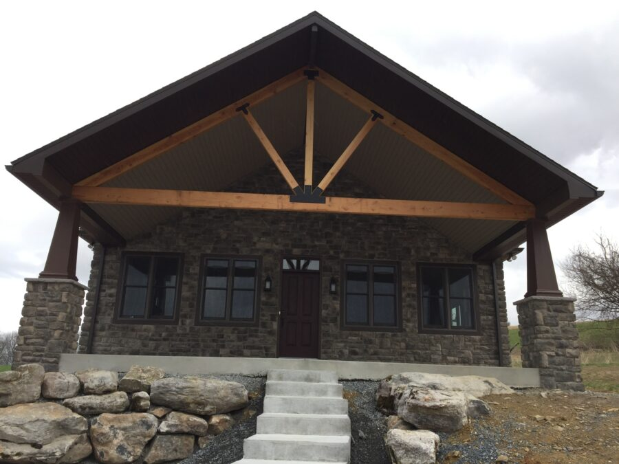 The enlarged front porch with stone pillars, painted craftsmen columns and a fir timer frame truss
