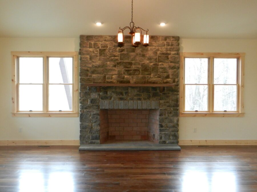 Great Room's wood-burning fireplace with full height stone surround & barn beam mantel with windows on each side & hardwood floors.