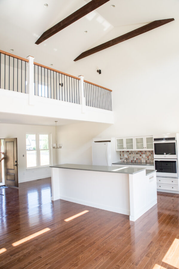 The open-concept main living space with views of the front door, the kitchen, dining room, great room and the loft above with white walls.