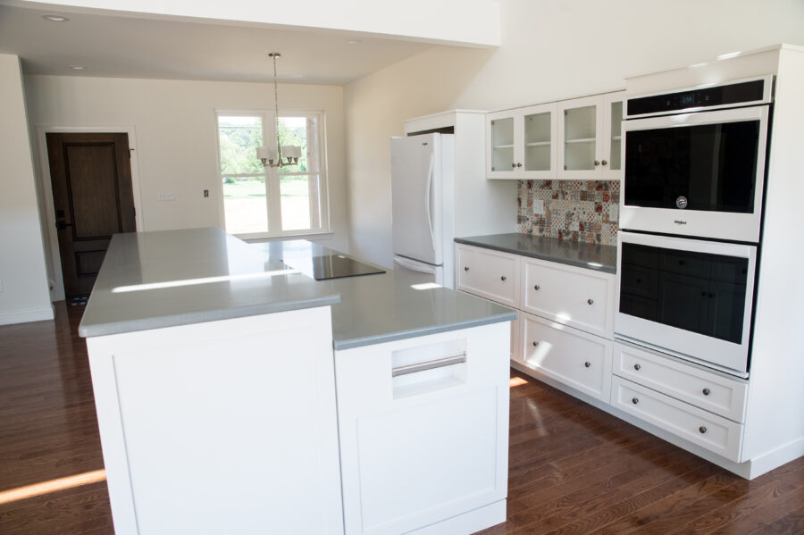 Fully custom kitchen with white walls, tile backsplash, white cabinets, and a center kitchen island
