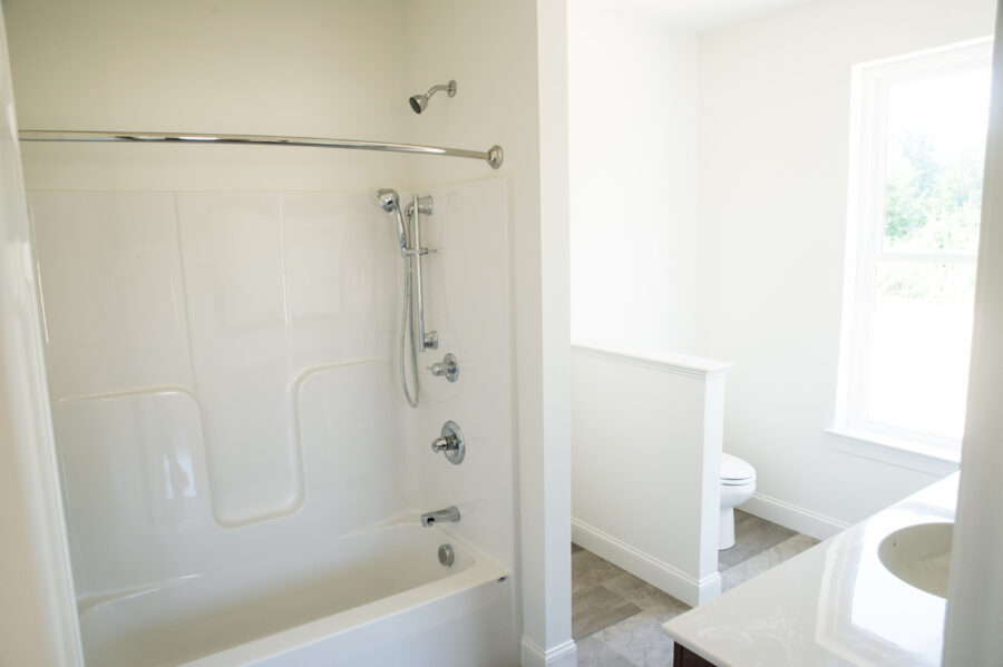 The white master bathroom with customized tub/shower faucets.