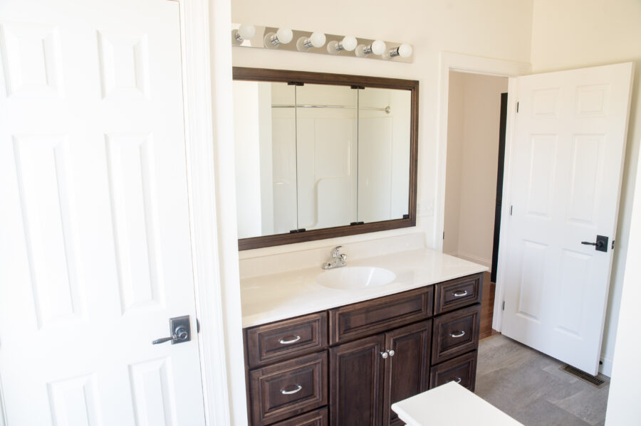 The custom-designed dark wood master bath vanity with a tri-view medicine cabinet recessed into the wall.
