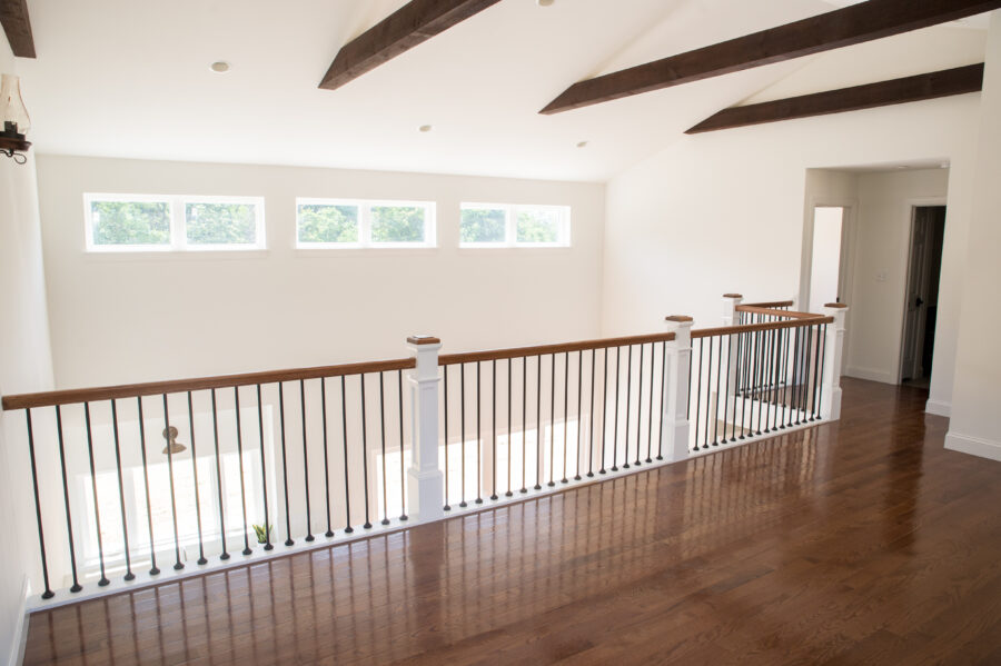 The loft with faux stained beams, small transom windows and black, round iron ballusters accent the loft area.