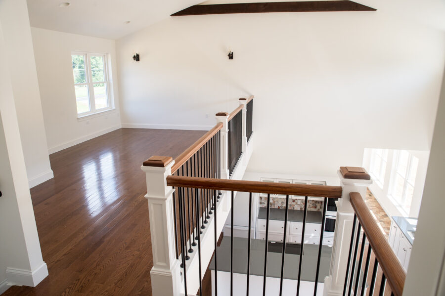 The large loft on the second floor with white walls and hardwood floors and black, round iron ballusters