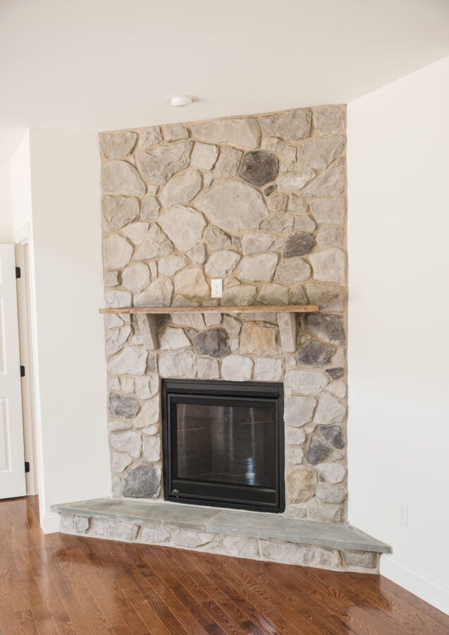 The corner gas fireplace with full height stone surround, raised hearth, and barn beam mantel in the great room.
