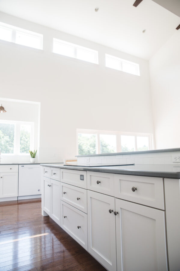 Custom painted, bright white kitchen cabinetry with grey quartz kitchen countertops in the kitchen.