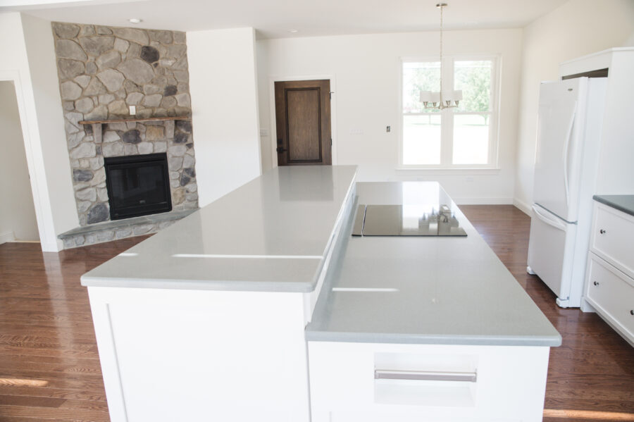 The white painted kitchen island with quartz countertops and a raised bar for kitchen seating