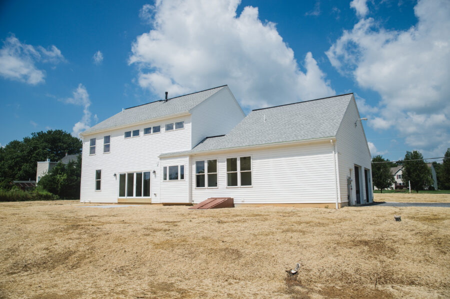 The rear of a custom-built Berks County home with white siding, a light grey roof and many windows