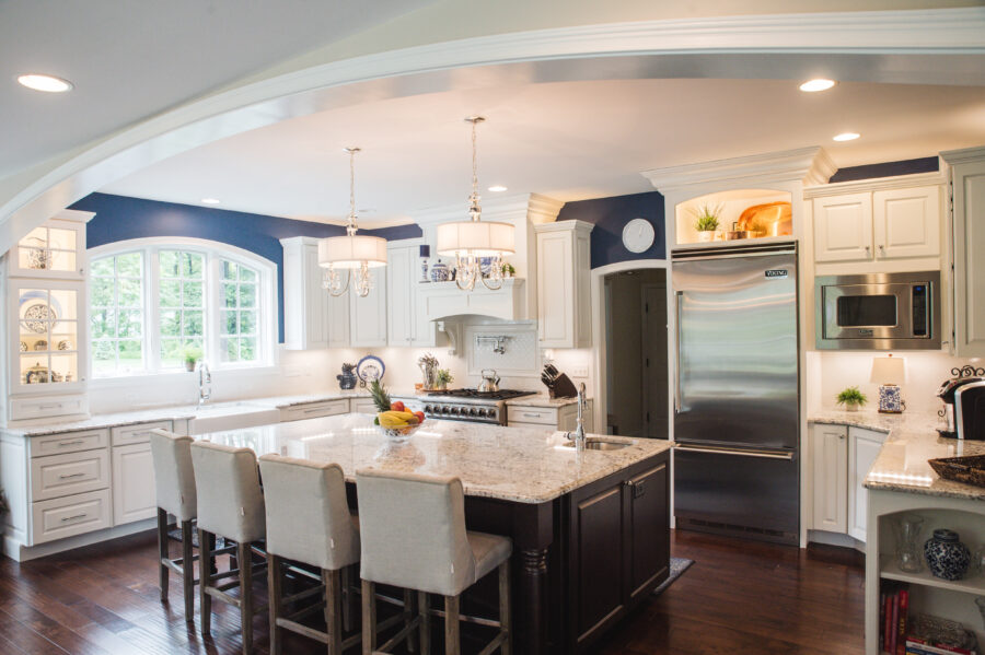 The customized kitchen has granite countertops, a window, an island with four chairs and a stainless steel refrigerator.