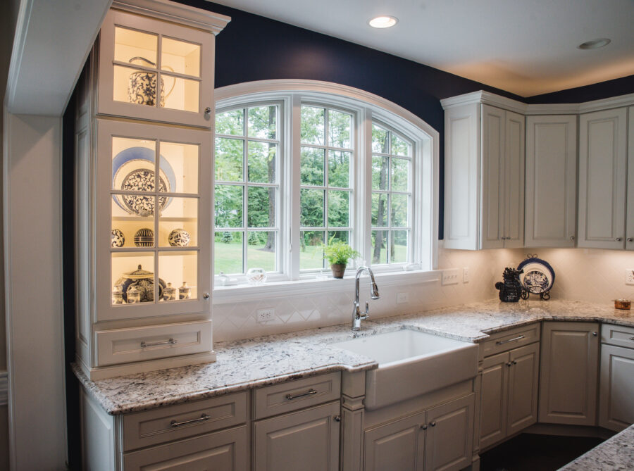 The kitchen wall has a customized arched window above the bumped out apron-front farmhouse sink with glass cabinets with internal lighting.