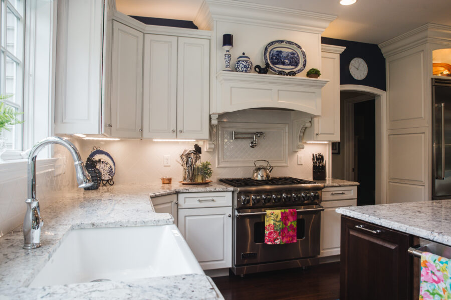 """The kitchen range wall with a 36"""""""" gar range stove with a pot filler and a raised decorative wood range hood with a subway tile backsplash."""