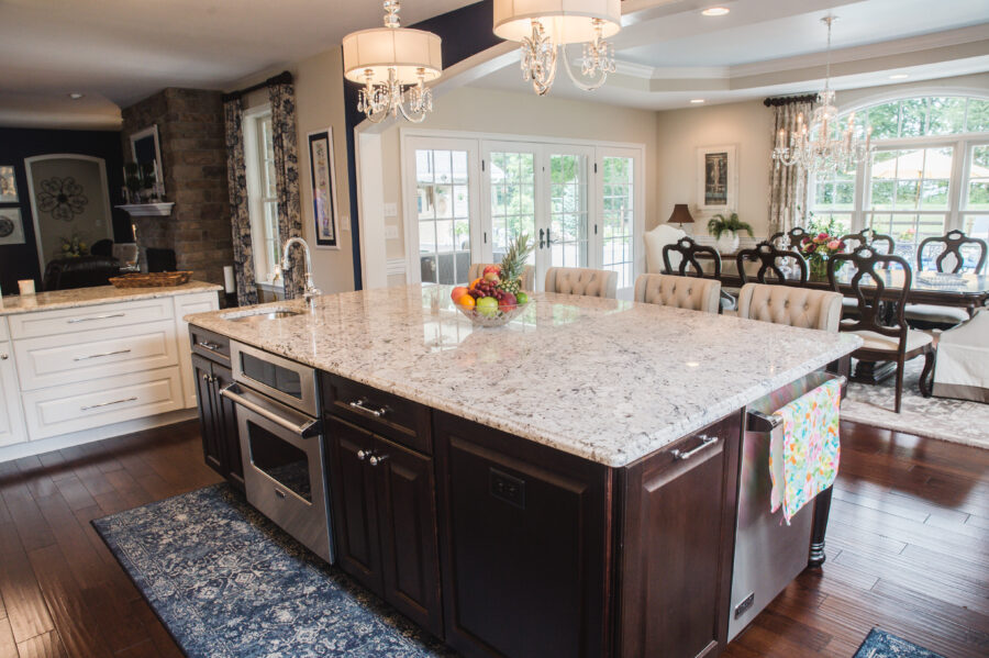 The oversized kitchen island with a prep sink, dishwasher and second oven built in with and overhang with extra seating.