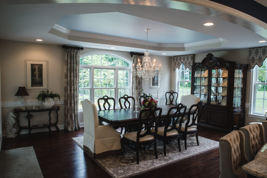 The large dining room with a table and eight chairs with a coffered ceiling with crown molding and multiple windows.