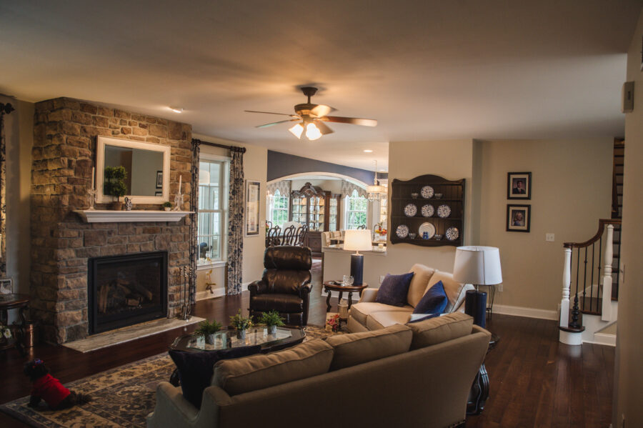 The family room has a couch, a loveseat, a chair, a coffee table, a stone fireplace, hardwood floors and views into the kitchen and dining room.
