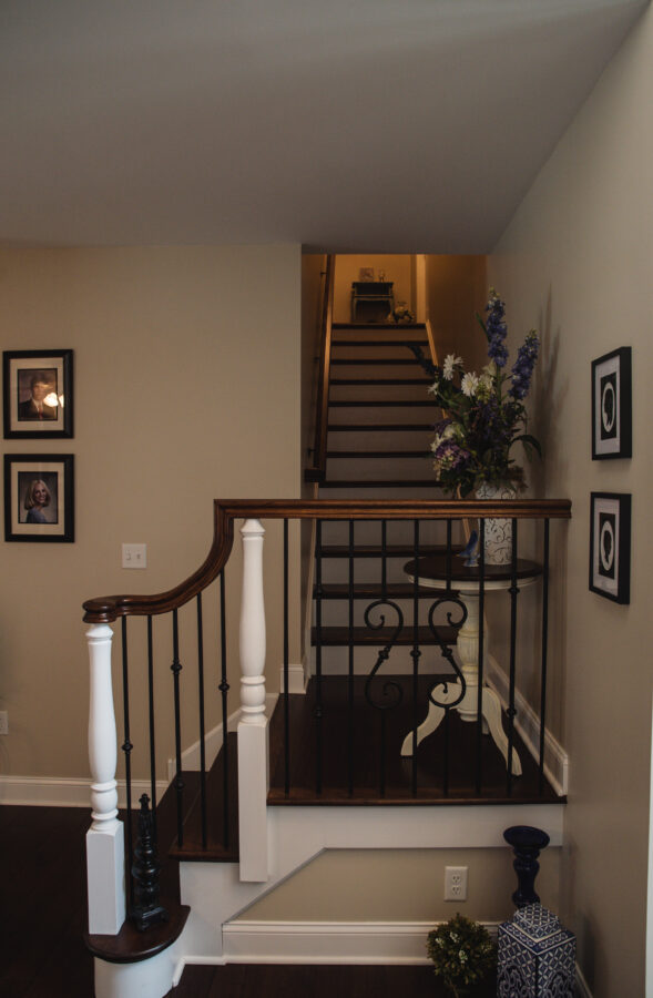 Iron railing with oak treads and riser stairs that lead up to the guest room suite.