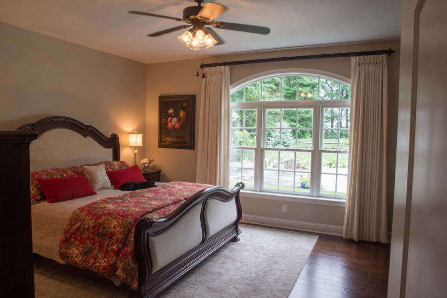 The Master Bedroom with an arched window and hardwood flooring with a bed and ceiling fan.