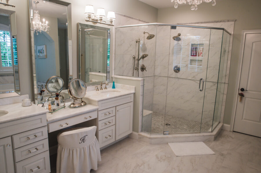 The Master Bathroom has custom cabinetry with double bowl sinks and a makeup vanity and a tiled shower with dual shower heads and a glass enclosure.