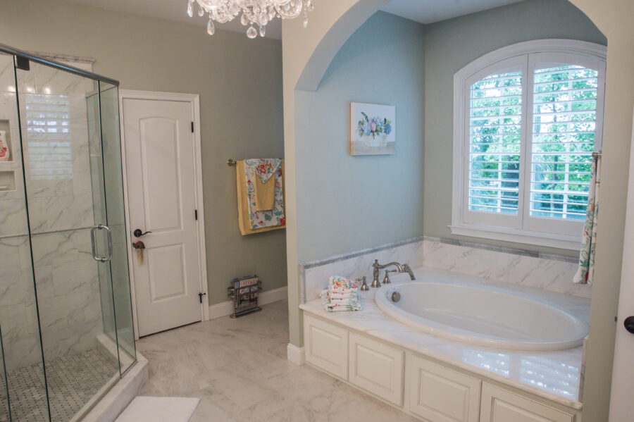 The Master Bathroom has a soaking tub with a granite top in front of an arched window.