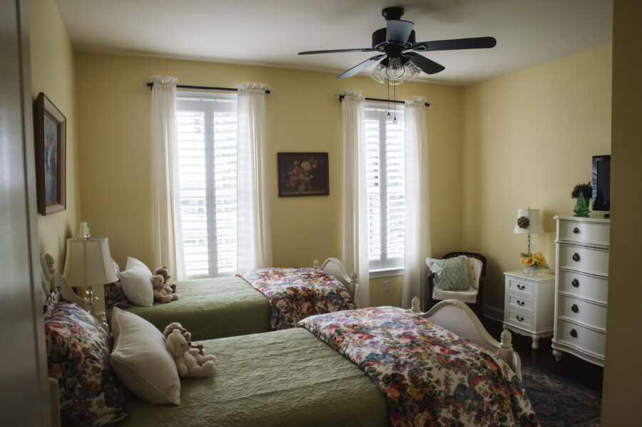 The second bedroom on the main level of the home has two beds, yellow walls, two windows and a ceiling fan.