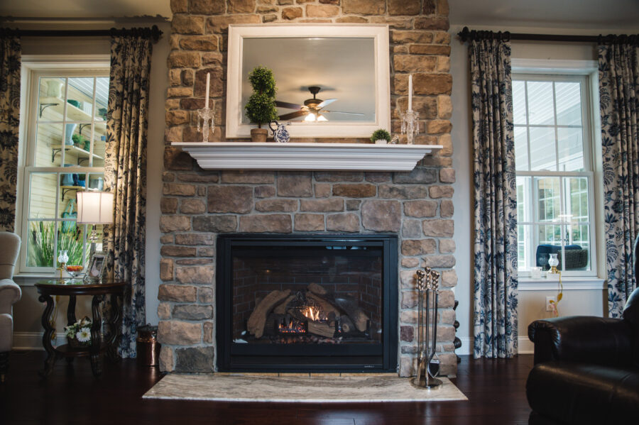 """The 42"""" gas fireplace with full-height stone surround with windows on both sides in the family room."""