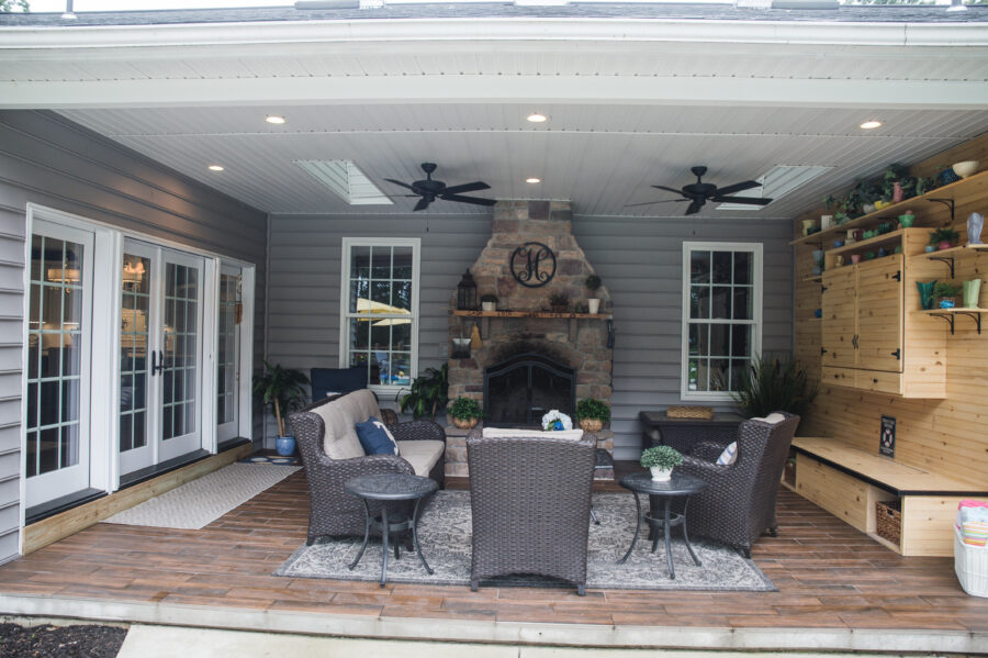The rear covered patio has a wood-burning fireplace with stone surround, two windows, wood flooring, a wood accent wall and patio furniture with two ceiling fans.