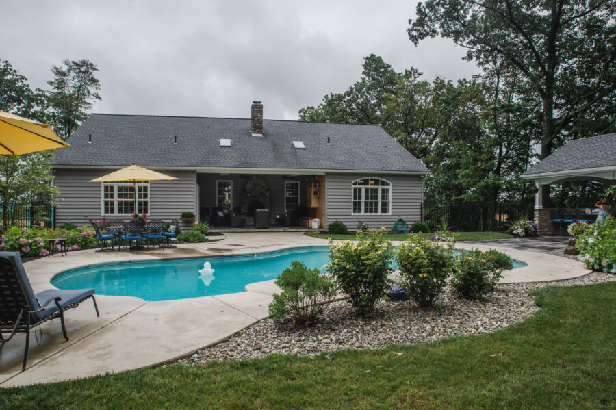 The back of the home has a backyard retreat with an in-ground pool and a rear covered patio.