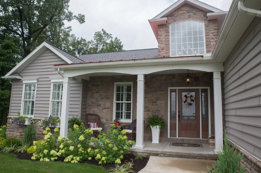 The welcoming Front Porch of the house with flowers in the front.