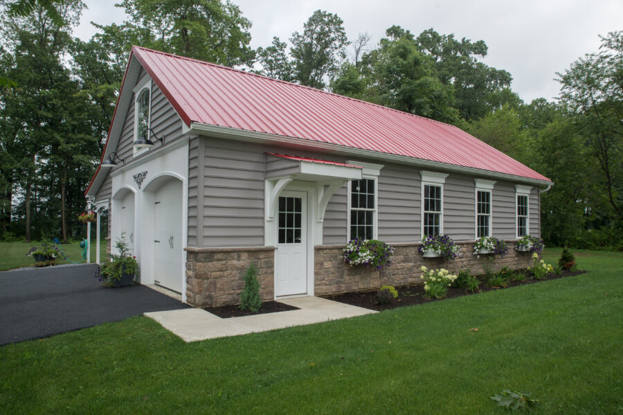 The detached garage with a red metal roof and a covered entry door with a flower bed in front.