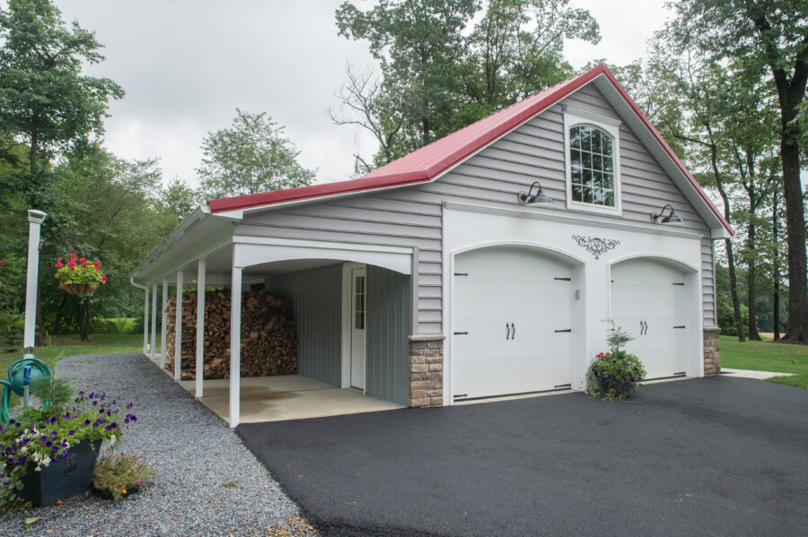 The detached garage with a red metal roof with a side awning to hide & dry chopped wood.