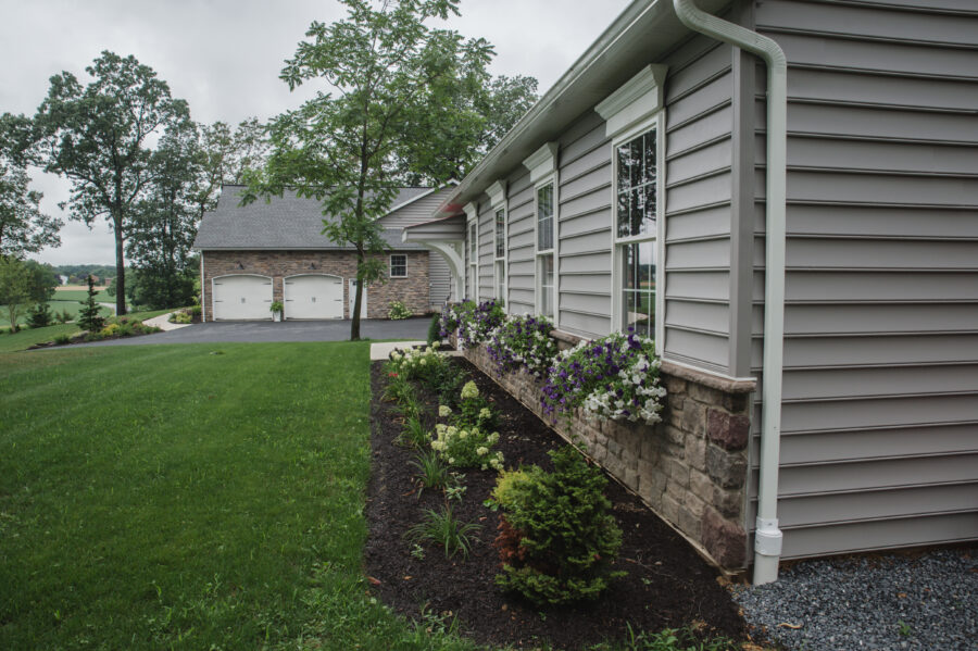 View of the home from the detached garage with a flower bed in front.