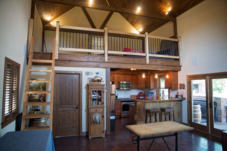 In inside of the pool house looking at the loft area above, with a full bath and kitchenette and ladder stairs.