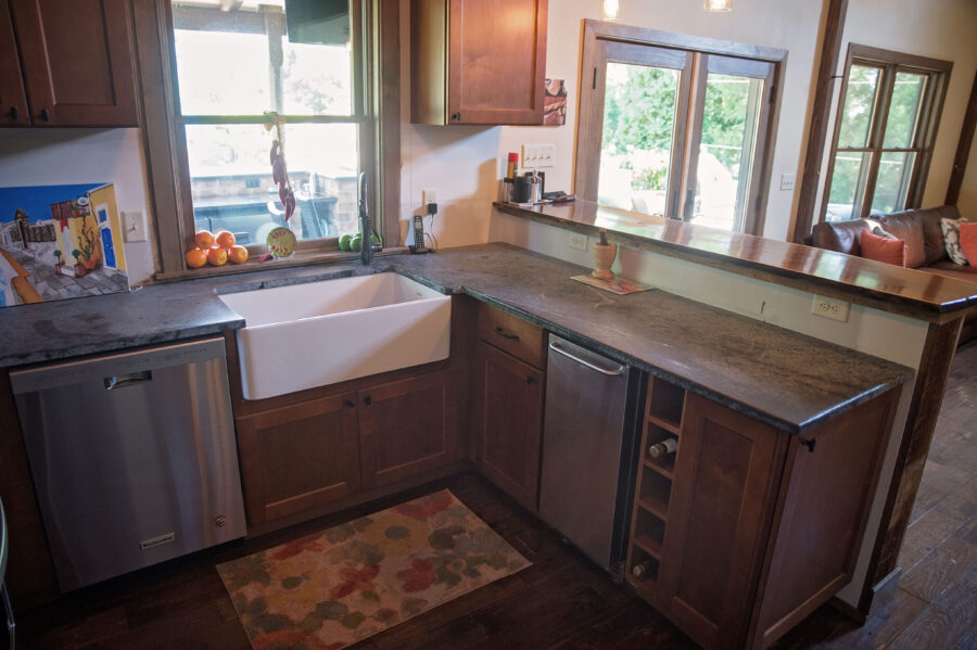 The concrete countertop in the kitchenette with an extra deep, single-bowl farmhouse sink and wood cabinets