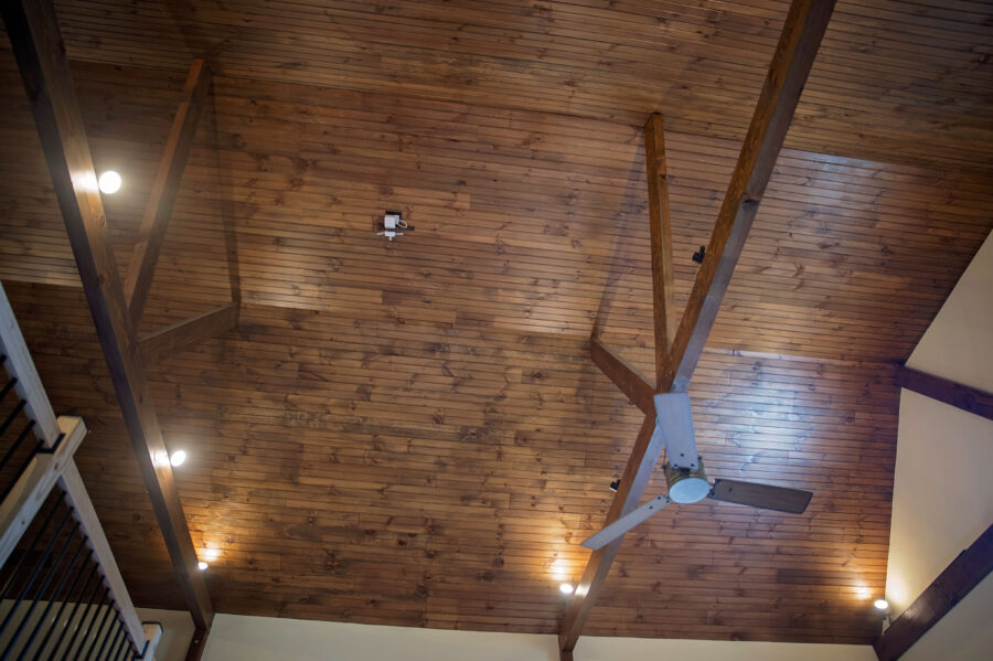 Cathedral Ceiling inside finished with stained wood panels and barn beams with a ceiling fan