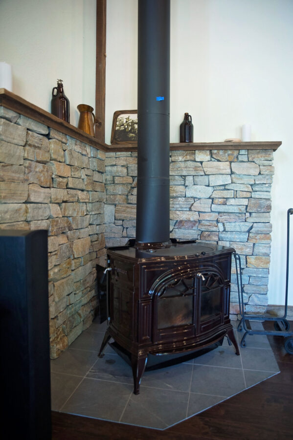 Wood stove in the corner of the great room with stone surround
