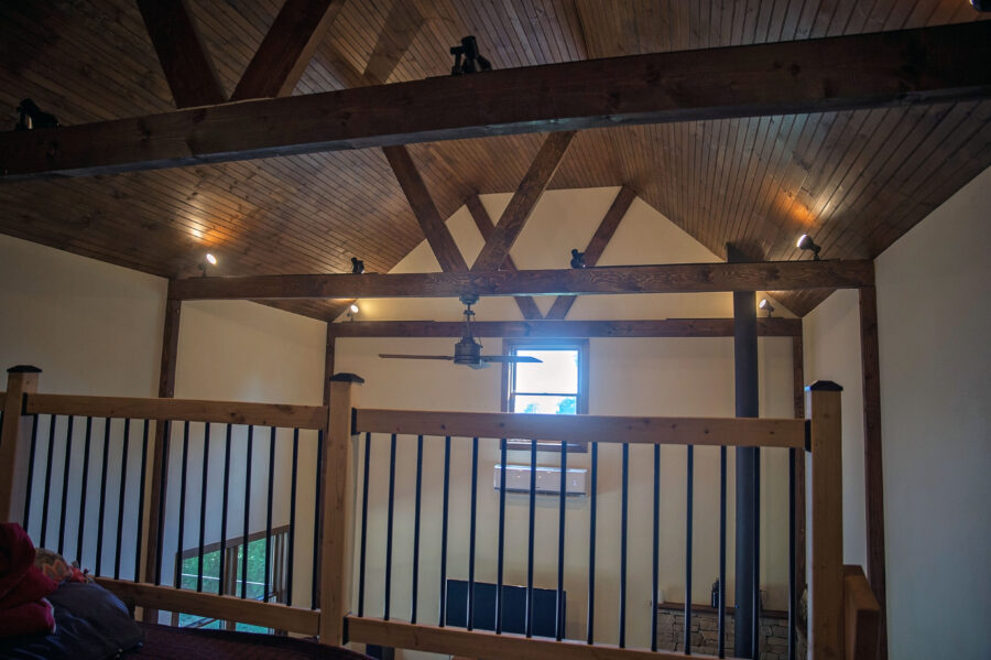 In the loft area overlooking the great room and cathedral ceiling with stained wood panels and barn beams with a ceiling fan