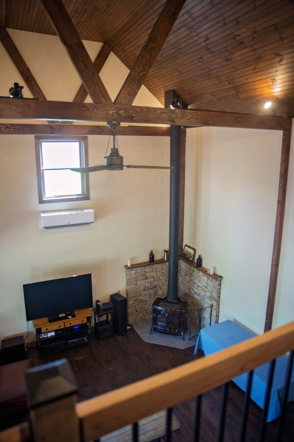 In the loft area overlooking the great room's corner fireplace with stone surround and ceiling beams and ceiling fan