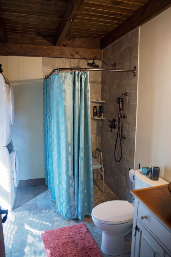 The full bathroom is ADA accessible with a tiled floor and tiled shower walls witha blue curtain and a washer & dryer
