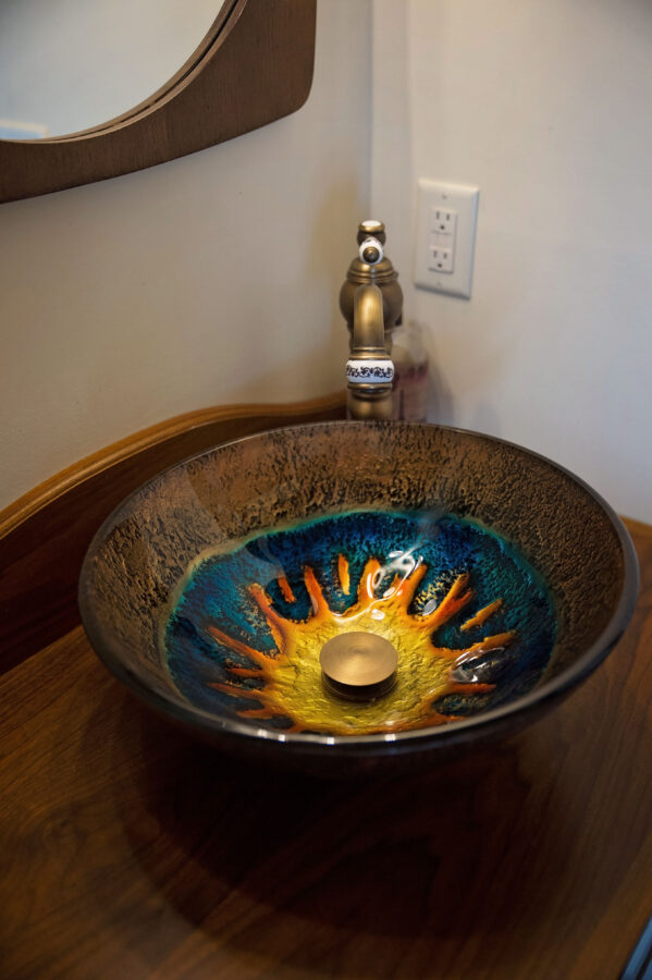 Custom cabinetry with vessel bown sink with a sun design in the sink bowl