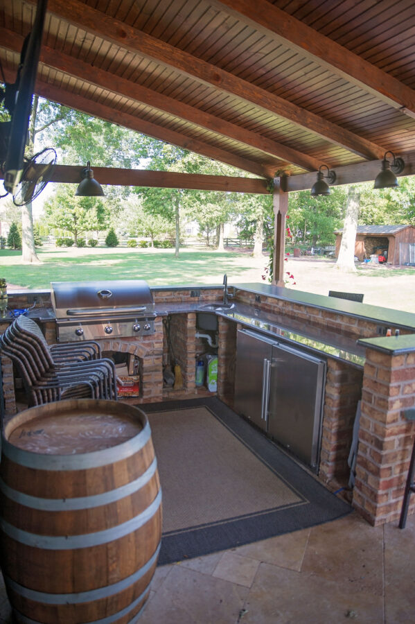 The bar area in the covered patio with a Built-In prep sink, freezer/refrigerator and gas grill