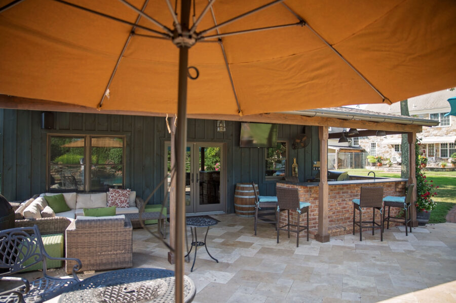 View of the large covered patio area with a brick front bar and lounge area