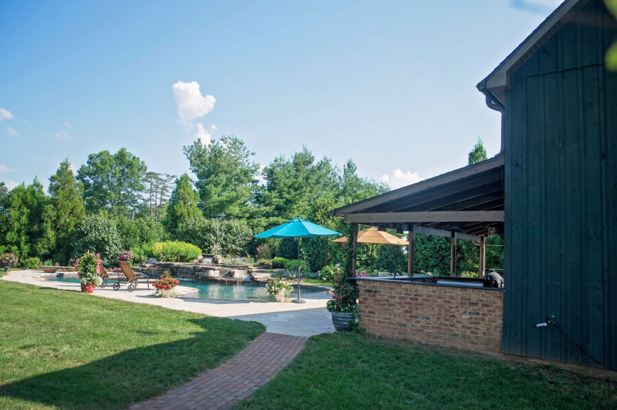 Side view of the pool house with a brick walkway and a brick front on the bar area with the pool in the background