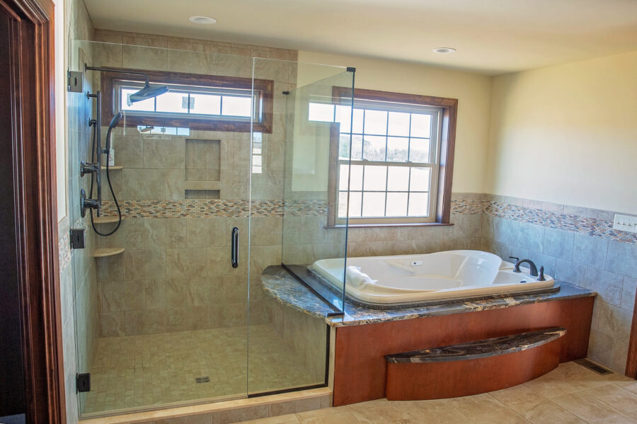 The Master Bathroom with a custom-designed tiled shower and a drop-in Whirlpool tub with oversized granite top under a large window.