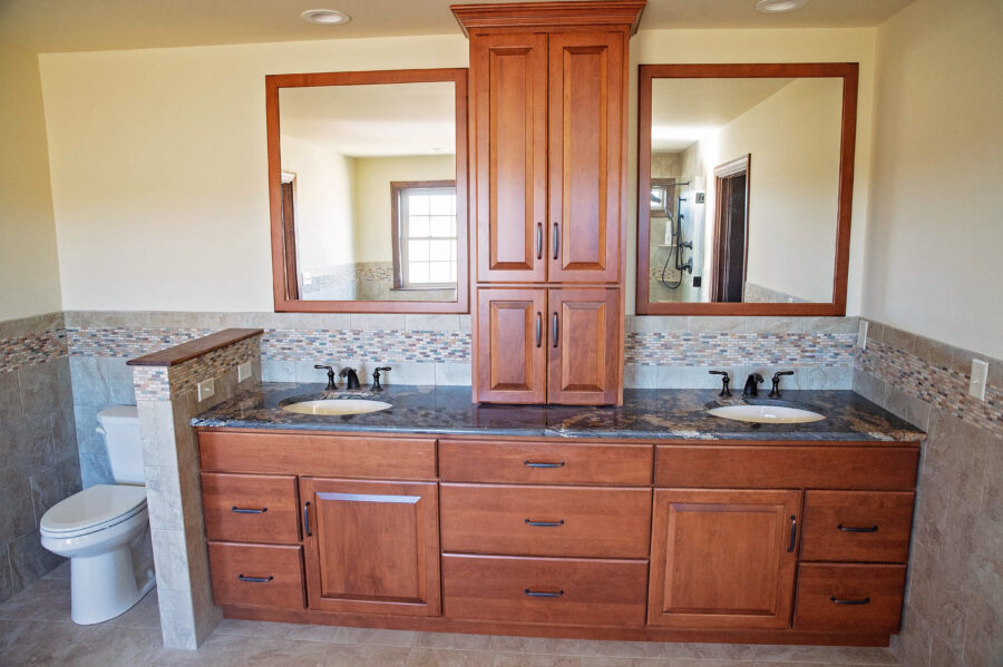 The Master Bathroom's customized double-sink vanity and granite countertops with tiled backsplash.