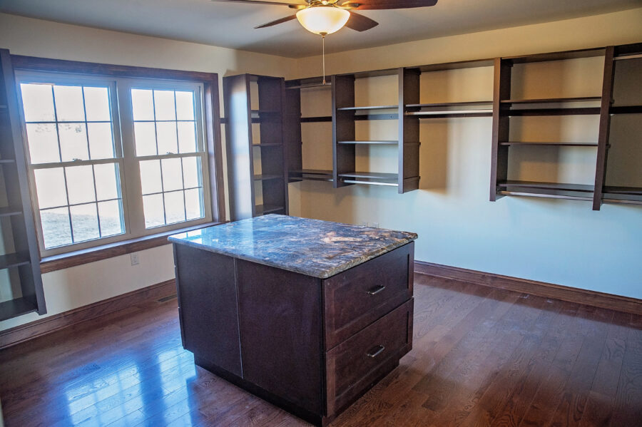 The Granite countertop on master bedroom closet island surrounded by ample shelving and natural light from a large window.
