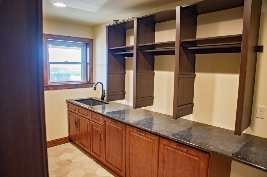 Laundry Room with custom-designed adjustable wooden shelving, custom-designed cabinetry and granite countertops and a drop-in Utility Sink