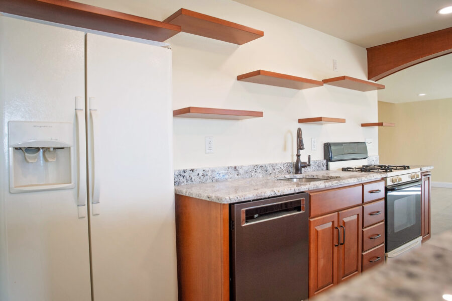 A complete Bar/Kitchen in finished basement with a refrigerators, stove and dishwasher with wood cabinetry.